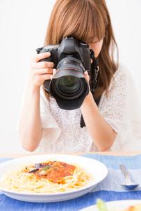料理を撮影する女性カメラマンの写真素材 [FYI02006805]