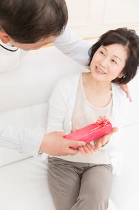 プレゼントを渡すシニア夫婦の写真素材 [FYI02006877]