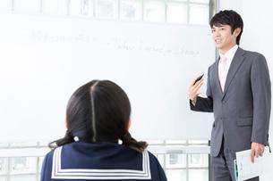 勉強する女子中学生と指導する講師の写真素材 [FYI02006892]