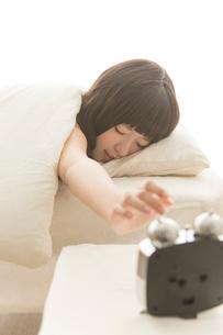 目覚まし時計を止めようとする女性の写真素材 [FYI02007123]