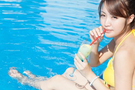プールサイドでカクテルを飲む女性の写真素材 [FYI02007128]