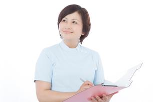 カルテに記入する看護師の写真素材 [FYI02007177]