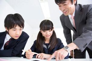 勉強する中学生と指導する講師の写真素材 [FYI02007189]