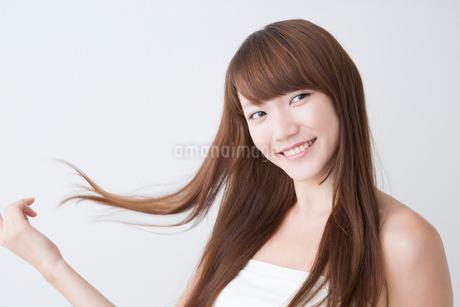 髪をなびかせて微笑む女性の写真素材 [FYI02007229]