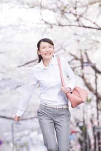 桜並木の下を走る女性の写真素材 [FYI02007251]