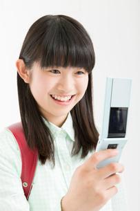 携帯電話を持つ女子小学生の写真素材 [FYI02007365]