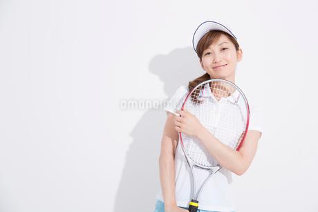 テニスラケットを持って微笑む女性の写真素材 [FYI02007379]