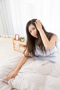 ベットから起きる女性の写真素材 [FYI02007399]