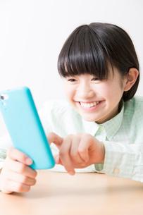 スマートフォンを触る女の子の写真素材 [FYI02007462]
