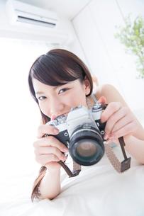 ベッドの上でカメラを構える女性の写真素材 [FYI02007464]