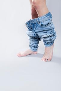 デニムパンツを脱ぐ女性の写真素材 [FYI02007557]