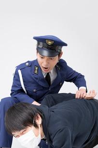犯人を捕まえる警察官の写真素材 [FYI02007789]