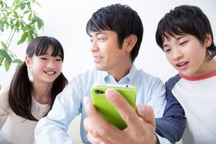 スマートフォンを見る親子の写真素材 [FYI02007833]