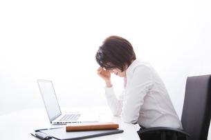 デスクワークに疲れるビジネスウーマンの写真素材 [FYI02007873]