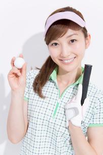 ゴルフボールを持って微笑む女性の写真素材 [FYI02007901]