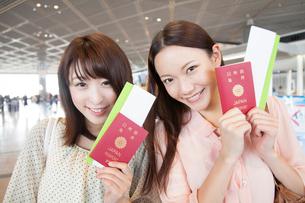 パスポートとチケットを持って微笑む女性達の写真素材 [FYI02007917]