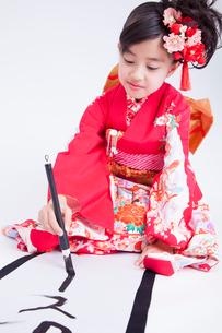 振り袖姿で書きぞめをする女児の写真素材 [FYI02008012]