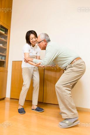シニア男性の歩行介助をする介護福祉士の写真素材 [FYI02008051]