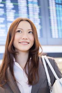 飛行機の時刻表の前で微笑むビジネスウーマンの写真素材 [FYI02008107]