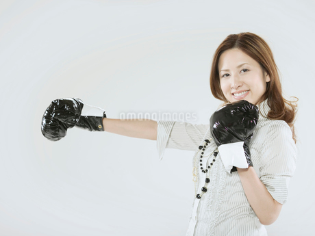 ボクシンググローブをつけた日本人OLの写真素材 [FYI02008386]