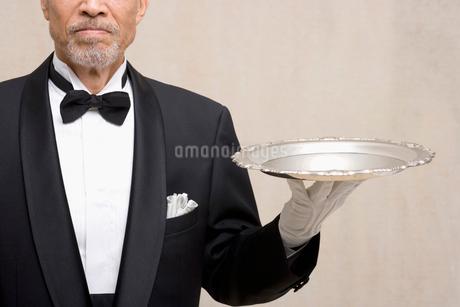 銀のトレイを持つシニア男性の写真素材 [FYI02008517]
