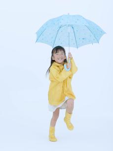 傘を持ち飛び跳ねる女の子の写真素材 [FYI02008597]