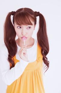 キャンディを舐める女性の写真素材 [FYI02009002]
