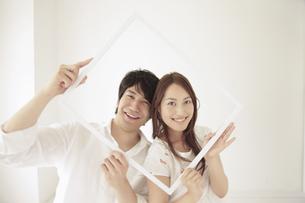 一つの額縁から顔を覗かせるカップルの写真素材 [FYI02009225]