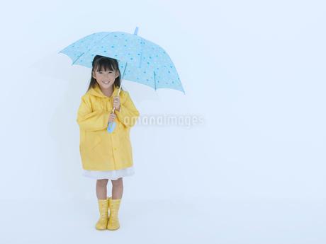 黄色い合羽を着て傘を差す女の子の写真素材 [FYI02009292]