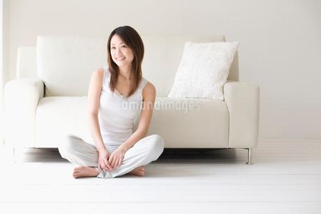 ソファの前であぐらをかく女性の写真素材 [FYI02009449]