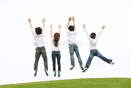 丘の上に一列に並びジャンプをする若者達の後ろ姿の写真素材 [FYI02009913]