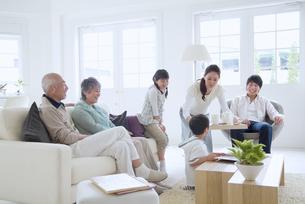 リビングでくつろぐ3世代家族の写真素材 [FYI02010172]