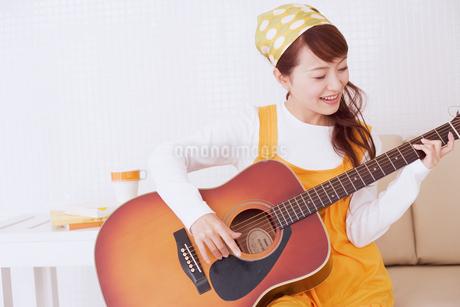 ギターを弾く女性の写真素材 [FYI02010372]