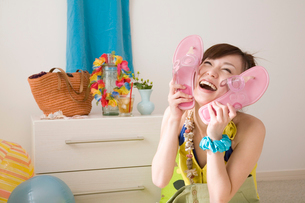 ビーチサンダルで顔を挟む笑顔の女性の写真素材 [FYI02010464]