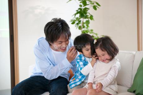 ソファに座る父親と子供達の写真素材 [FYI02010472]
