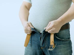 ベルトを外すお腹の出た男性の写真素材 [FYI02010560]