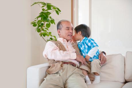ソファに座るおじいちゃんと男の子の写真素材 [FYI02010867]