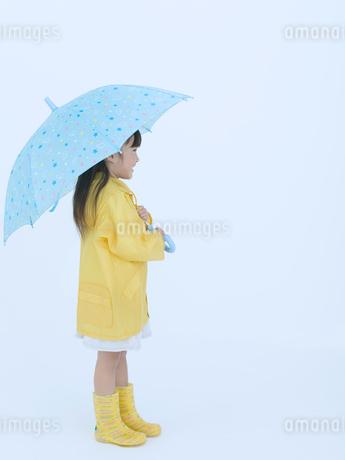 黄色い合羽を着て傘を差す女の子の横顔の写真素材 [FYI02010929]