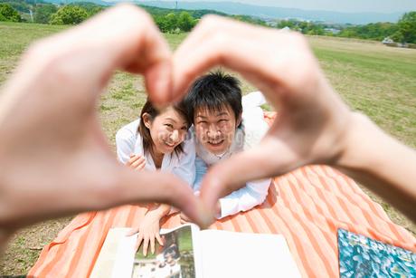 手で作ったハートの向こうの日本人カップルの写真素材 [FYI02011032]