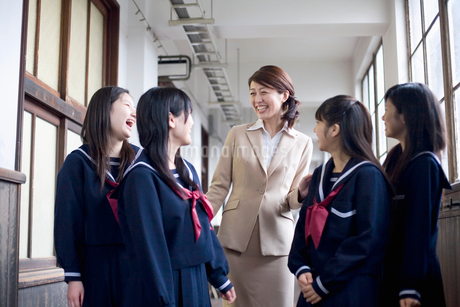 廊下で話をする先生と女子中学生4人の写真素材 [FYI02011124]