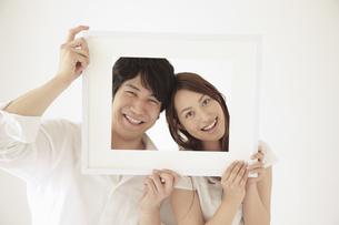 一つの額縁から顔を覗かせるカップルの写真素材 [FYI02011177]