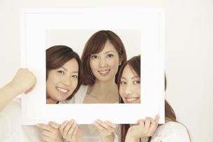 一つの額縁から顔を覗かせる3人の女性の写真素材 [FYI02011298]