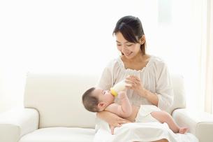 お母さんに抱かれてミルクを飲む赤ちゃんの写真素材 [FYI02011308]