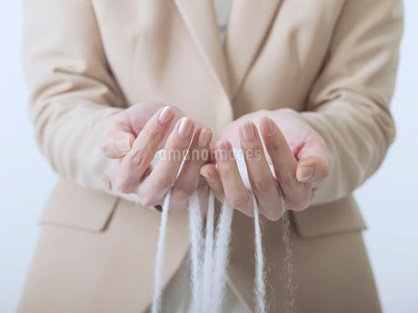 手から零れる白い砂の写真素材 [FYI02011379]
