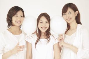 白い風船を顔で挟む3人の女性の写真素材 [FYI02011389]