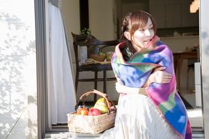 食材の入った籠とブランケットに包まる女性の写真素材 [FYI02011475]