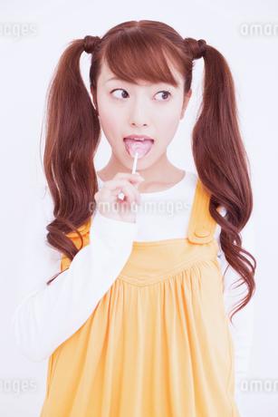 キャンディを舐める女性の写真素材 [FYI02011595]