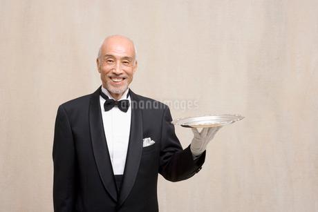 銀のトレイを持つシニア男性の写真素材 [FYI02011613]