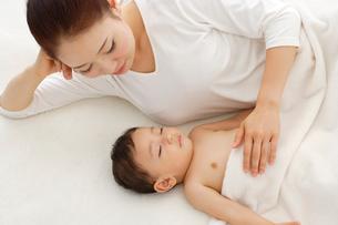 眠る赤ちゃんと添い寝をするお母さんの写真素材 [FYI02012844]