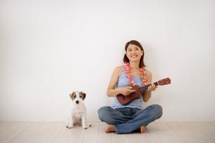 床に座ってウクレレを弾く女性と犬の写真素材 [FYI02013046]